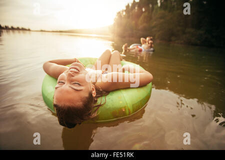 Closeup portrait of young woman with her eyes closed relaxing on inflatable ring in lake on a sunny day. - Stock Photo