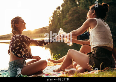 Group of young women celebrating at a lake. Young friends are toasting each other with beers during sunset at the - Stock Photo