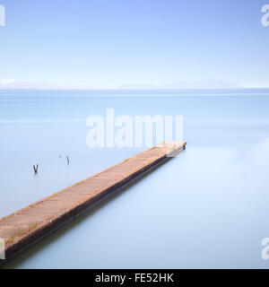 Concrete pier or jetty on a blue sea. Hills on background. Long exposure photography in Lido Camaiore, Versilia, - Stock Photo