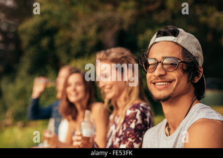 Portrait of happy young man at a lake with friends sitting by. Young friends hanging out at the lake. - Stock Photo