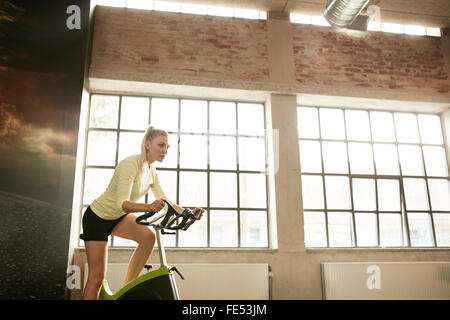 Fitness woman exercising on a spinning cycle in gym. Caucasian young female athlete doing fitness training on a - Stock Photo