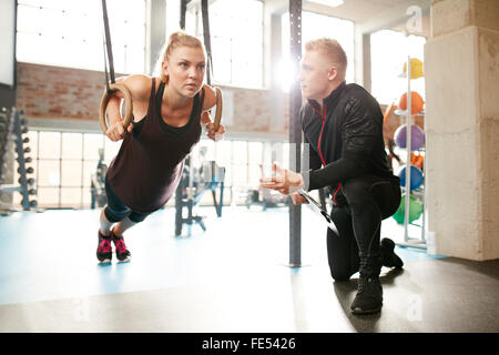 Young woman is doing exercises with the help of a personal trainer in a modern gym. Female working out on gymnastic - Stock Photo