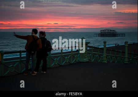 Brighton, UK. 4th February 2016. UK Weather. Couples enjoying the last of a spectacular sunset along Brighton seafront. - Stock Photo