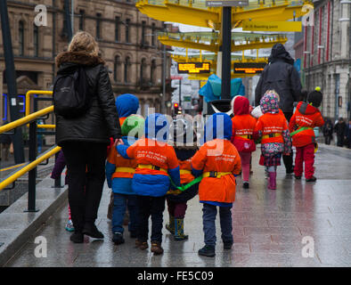 School children safeguarded, wearing protective fluorescent hi-vis hazard jackets during the Chinese New Year, Manchester, - Stock Photo