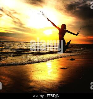 Woman Jumping On Sandy Beach During Sunset - Stock Photo