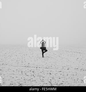 Rear View Of Woman Doing Yoga In Snowy Field - Stock Photo