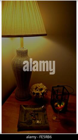 Lit Electric Lamp And Flowers In Vase On Table - Stock Photo