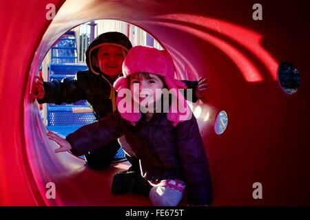 Children In Playground Tunnel - Stock Photo