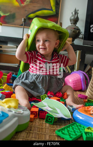 A baby girl (age 15 months) has fun putting a plastic box over her head as she plays with Lego and other toys in - Stock Photo