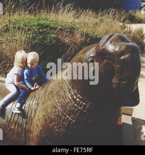 High Angle View Of Siblings Sitting On Animal Statue - Stock Photo