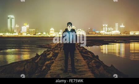 Portrait Of Young Man Standing On Pier Amidst River At Night