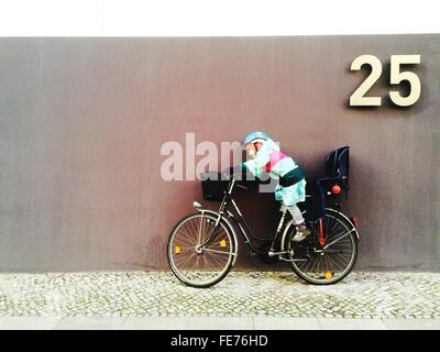 Boy On Bicycle Against Wall - Stock Photo