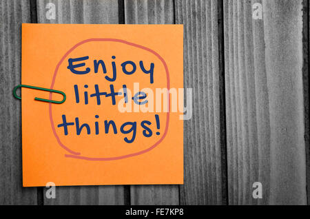 Enjoy little things word on orange notes - Stock Photo