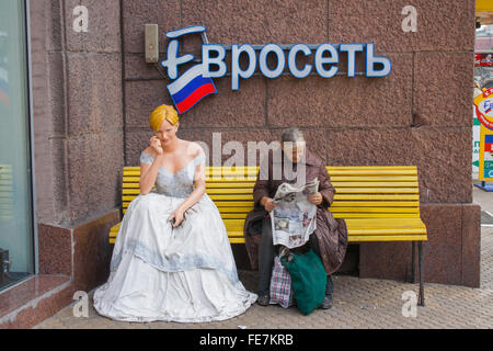 Poor elderly lady reading newspaper next to a mannequin in a ball gown, Moscow, Russia - Stock Photo