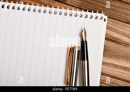 Blank notebook with fountain pen on wooden table - Stock Photo
