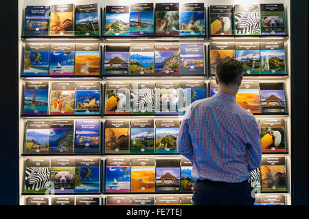 London, UK.  4 February 2016. A visitor admires travel brochures to exotic places on the opening day of 'Destinations: - Stock Photo