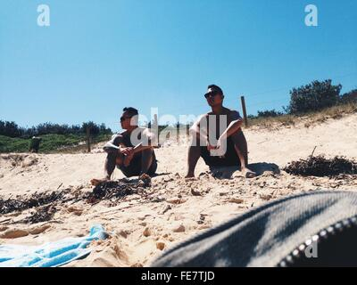 Low Angle View Of Friends Relaxing On Sandy Beach - Stock Photo