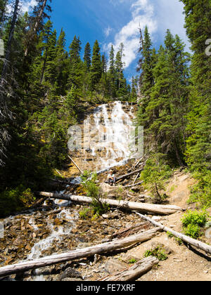 A woman enjoys sitting in Point Lace Falls on a beautiful summer day; Yoho National Park, near Field, British Columbia, - Stock Photo