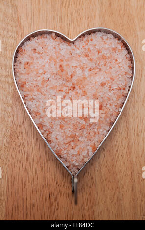 Heart filled with Himalayan salt on a wooden board - Stock Photo
