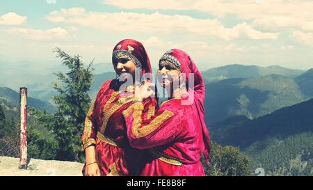 Mother And Daughter In Traditional Clothing Against Mountains - Stock Photo