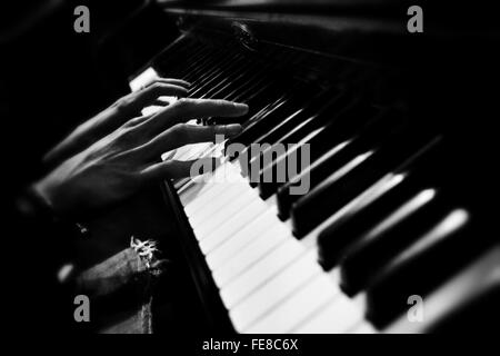 Close-Up Of Person Hands Playing Piano - Stock Photo