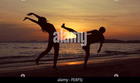 Silhouette Man Hitting Woman On Beach At Sunset - Stock Photo
