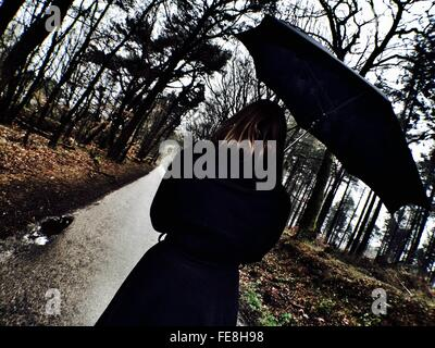 Rear View Of Woman Holding Umbrella Walking On Pathway Amidst Trees - Stock Photo