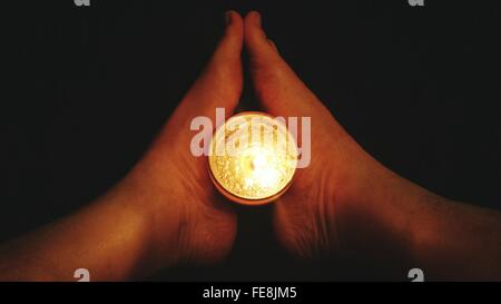 Close-Up Of Legs Holding Torch Over Black Background - Stock Photo
