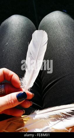 Close-Up Of Hand Holding Feather - Stock Photo