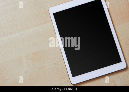 Tablet seen from above on a wooden desk, blank screen - Stock Photo
