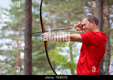 Man hunter shot with bow in open air - Stock Photo