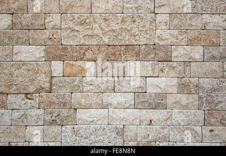 Part of the wall of natural stone beige porous structure. Finishing stone rectangular different shape and size. - Stock Photo