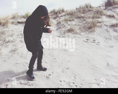 Teenage Girl Looking At Footprints On Sand - Stock Photo