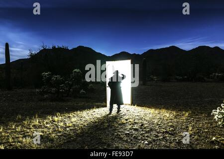 Rear View Of Silhouette Man Standing In Front Of Illuminated Door On Field Against Sky At Dusk - Stock Photo