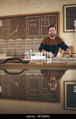 Portrait of a professional craftsman working in his studio on a project - Stock Photo