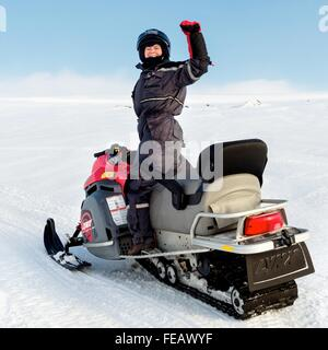 Woman on snowmobile on glacier in Iceland. - Stock Photo