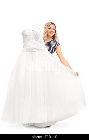 Vertical shot of a young woman holding a white wedding dress isolated on white background - Stock Photo