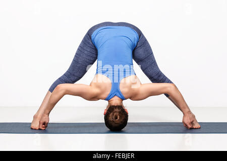 Woman practices Ashtanga Vinyasa yoga asana - Stock Photo
