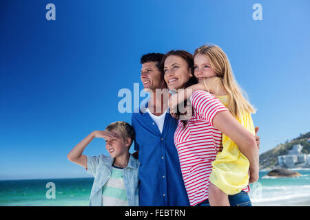 Cute family smiling and mother giving piggy back to her daughter - Stock Photo