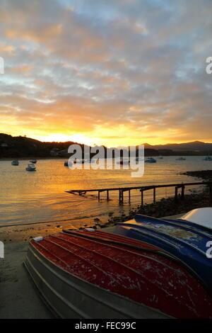 Fishing boats at rest in Moeraki Bay during sunset at Moeraki in Otago, New Zealand. - Stock Photo