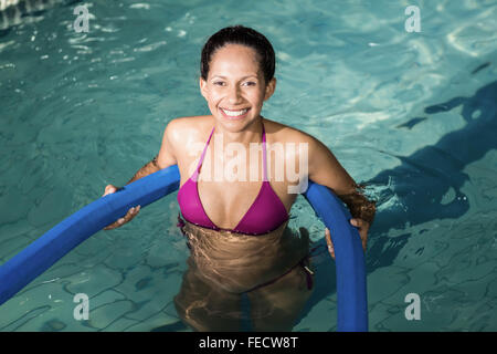 Happy pregnant woman exercising in the pool - Stock Photo