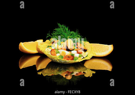 Salad of mussels with corn and peas in the leaves of savoy cabbage on a black background - Stock Photo