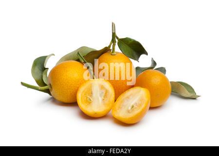 Fresh round half and whole kumquats on white background - Stock Photo