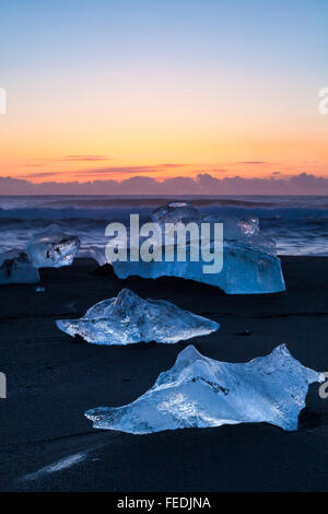 Blocks of ice at Jokulsarlon Glacial beach, Diamond beach at sunrise, Iceland in January - icebergs - Stock Photo