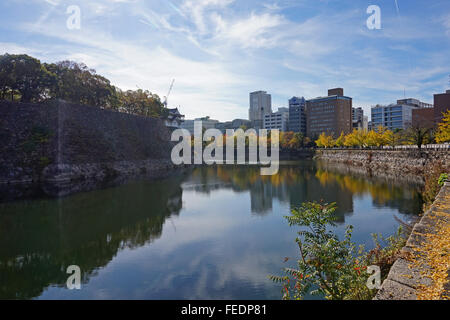 The moat and ramparts around Osaka-jo castle, with Osaka's modern buildings behind, Japan - Stock Photo