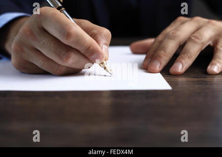 Man signing a document or writing correspondence with a close up view of his hand with the pen and sheet of notepaper - Stock Photo