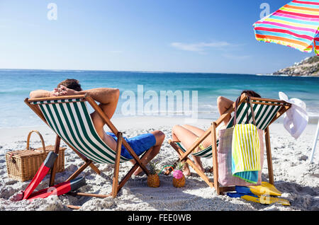 Cute couple lying on deckchairs - Stock Photo
