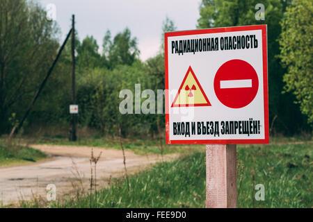 Ionizing radiation warning sign near the village in the Gomel region of Belarus. Radiation contamination area. - Stock Photo