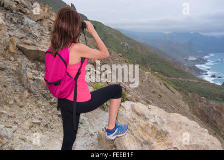 Hiker woman on top of the mountain looking through binoculars - Stock Photo