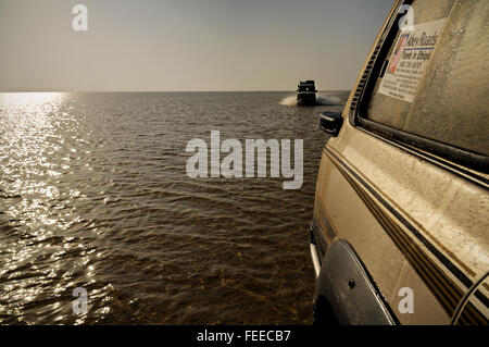 Two off-road vehicles crossing the low-water Lake Assale in the Danakil depression at sunrise, Afar Region, Ethiopia - Stock Photo